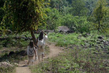 A young Tyronan family walking home along a small dusty trail through the forest.