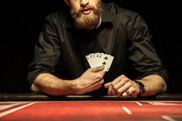 Cropped shot of bearded man showing poker cards