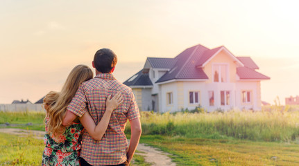 Young Couple Standing Outside Dream Home