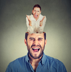 young angry woman screaming inside head of a frustrated guy