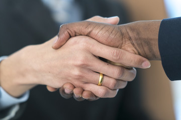 Close up of caucasian and African business people shaking hands