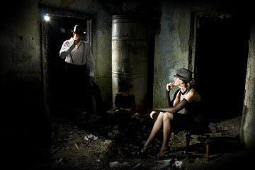 Conceptual photo. Young woman is sitting on a chair and man is standing next to her with gun in hands. They are dressed in retro style. Ruined place.