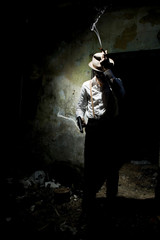 Portrait of a gangster dressed in retro suit with hat, smoking cigar and holding gun in hands. Ruined place.