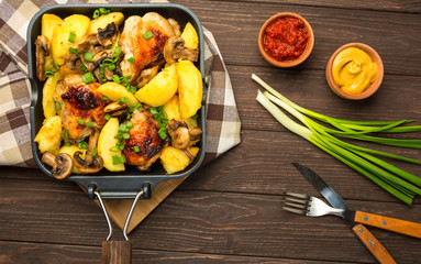 Dinner with baked chicken legs with olives spiced with aromatic herbs and potatoes with mushrooms on a rustic background. Top view, copy space.