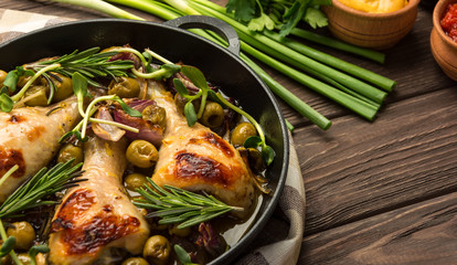 Baked chicken legs with olives spices and herbs on a rustic background. Copy space.