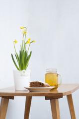 Fototapeta ciasto, herbata i kwiaty żonkile na stole obraz