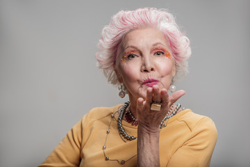Happy elderly female posing with bright make-up