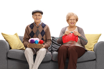 Seniors sitting on a sofa and knitting together