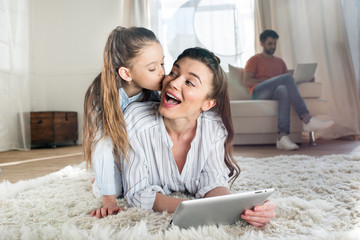 Mother and daughter having fun while lying on carpet and using digital tablet