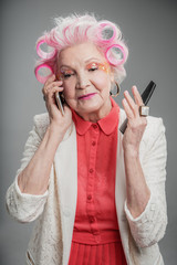 Pleasant senior adult lady with hair curlers using cellphone
