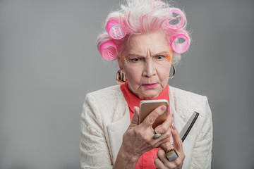 Serious elderly lady holding cellphone and comb