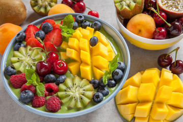 breakfast green smoothie bowl with fruits and berries