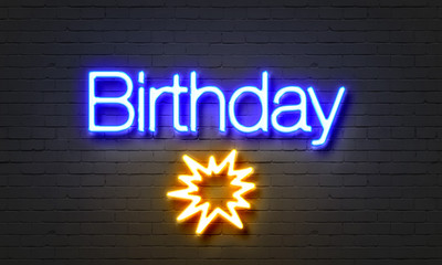 Birthday neon sign on brick wall background.