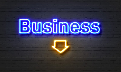 Business neon sign on brick wall background.