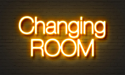 Changing room neon sign on brick wall background.