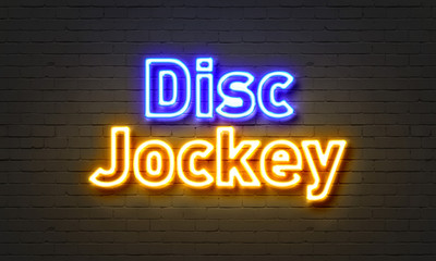 Disc jockey neon sign on brick wall background.