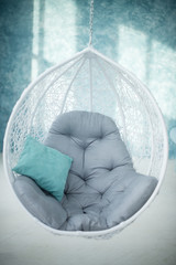 Swing chair decorated with pillow on blue background. Rest area