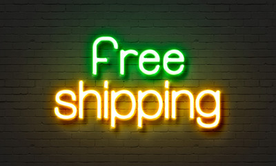 Free shipping neon sign on brick wall background.