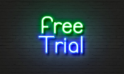 Free trial neon sign on brick wall background.