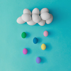 Cloud and rain made of colorful easter eggs on blue background. Flat lay. Minimal concept.