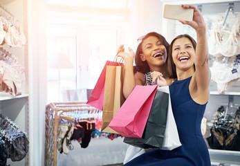 Two vivacious fun loving young women shoppers