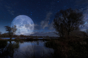 Night landscape with the Moon over the Dnieper river in Kiev, Ukraine, during autumn
