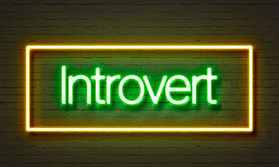Introvert neon sign on brick wall background.