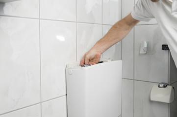 Handwerker repariert Toilettenspülung.