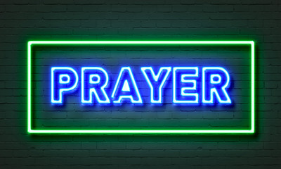 Prayer neon sign on brick wall background.