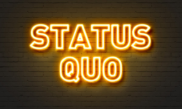 Status quo neon sign on brick wall background.