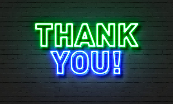 Thank you neon sign on brick wall background.