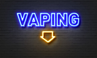 Vaping neon sign on brick wall background.