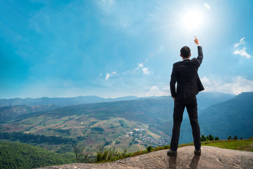 Back of successful businessman pointing up with his finger standing on top of mountain with sunlight sky background. Young man reaching goal, success and achievement in his life. Copy space.