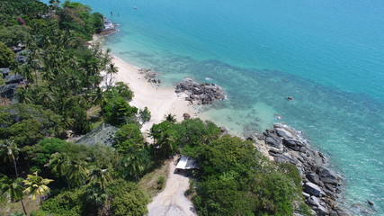 Aerial view of sea coastline and island with palm trees in Phuket, Thailand