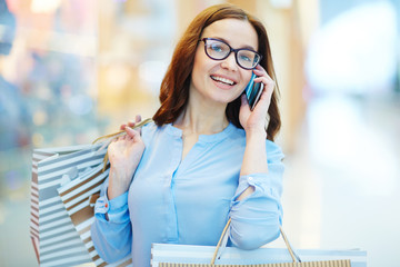 Woman with smartphone calling in shopping-center