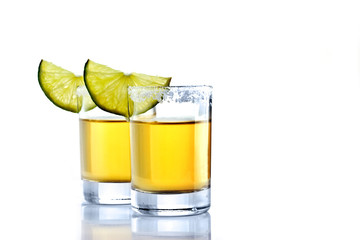 Shot of golden tequila with lime on a white background for isolation
