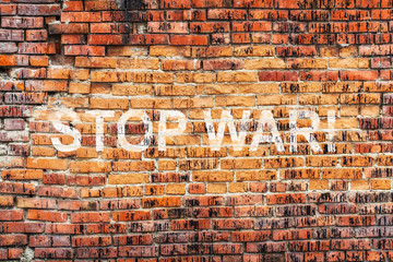 Text STOP WAR on stained old orange brick wall texture background