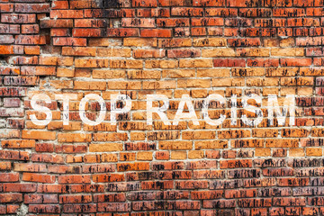 Text STOP RACISM on stained old orange brick wall texture background