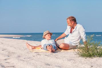Father with son take a sun bath on the sea beach
