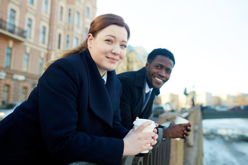 Portrait of two business colleagues leaning on river bank railing and looking at camera, smiling while holding disposable coffee cups both wearing coats