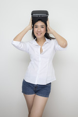 Technology series: Asian woman wearing VR glasses against white background