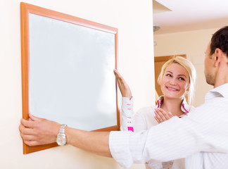 Young couple hangs a picture