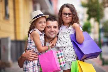 Happy daughters hugging father with shopping bags
