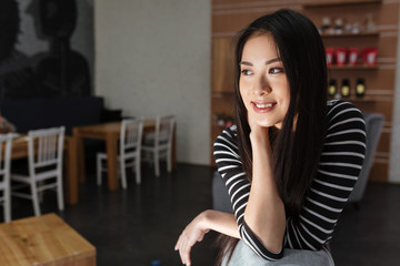 Pensive Smiling Asian woman sitting in cafeteria