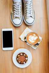 Top view of wooden board with phone, coffee