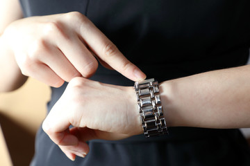 woman watching and pointing to the wrist watch