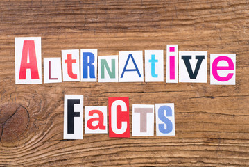 "Phrase ""Alternative Facts"" in cut out magazine letters on wooden background"
