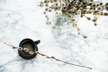 morning coffee on a marble table with a bunch of willow twigs. texture, background, copyspace