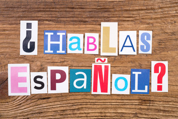 "Question ""Hablas Espanol?"" in cut out magazine letters on wooden background"
