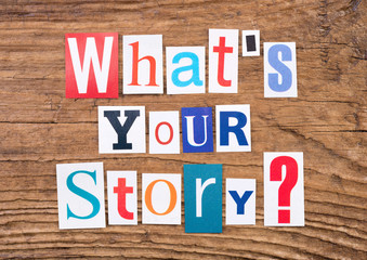 "Question ""What's your story?"" in cut out magazine letters on wooden background"